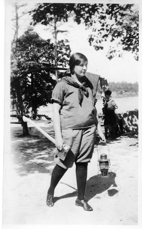 Old photo of girl scout with axe and lantern